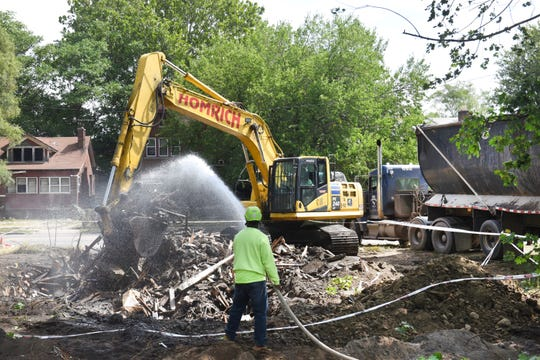 A worker for city contractor Homrich hoses down dirt and debris as an excavator removes material from the site where a home was torn down along Wyoming south of I-96 in Detroit on Aug. 26.