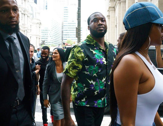 Rapper Meek Mill, center, arrives at the Criminal Justice Center in Philadelphia on Tuesday, Aug. 27, 2019.  Mill will learn if Philadelphia prosecutors will drop a 2007 case that's kept him under court supervision for more than a decade.