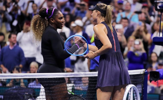 Serena Williams, left, shakes hands with Maria Sharapova after their first-round match Monday at the U.S. Open tennis tournament.