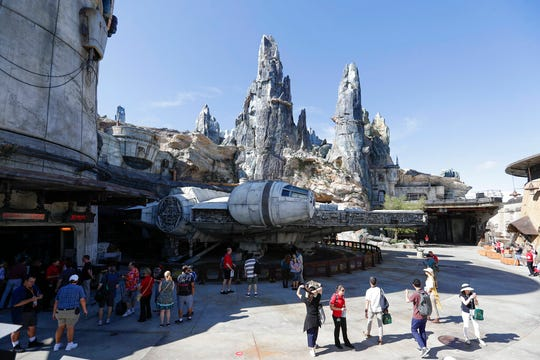 Park visitors walk near the entrance to the Millennium Falcon Smugglers Run ride during a preview of the Star Wars themed land, Galaxy's Edge in Hollywood Studios at Disney World, Tuesday, Aug. 27, 2019, in Lake Buena Vista, Fla. The attraction will open Thursday to park guests.