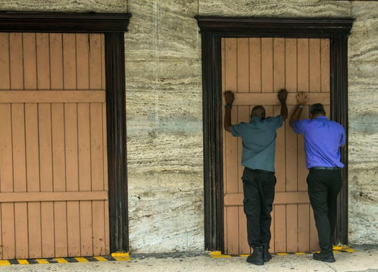 Residents board up a storefront pharmacy as they prepare for the arrival of Tropical Storm Dorian, in Bridgetown, Barbados, Monday, Aug. 26, 2019. Much of the eastern Caribbean island of Barbados shut down on Monday as Dorian approached the region.