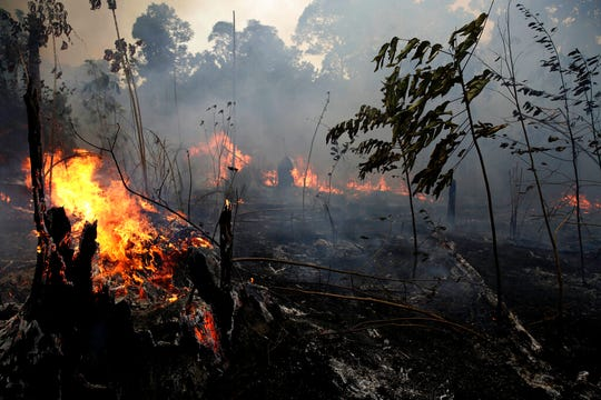 "A fire burns trees and brush along the road to Jacunda National Forest, near the city of Porto Velho in the Vila Nova Samuel region which is part of Brazil's Amazon, Monday, Aug. 26, 2019. The Group of Seven nations on Monday pledged tens of millions of dollars to help Amazon countries fight raging wildfires, even as Brazilian President Jair Bolsonaro accused rich countries of treating the region like a ""colony."""