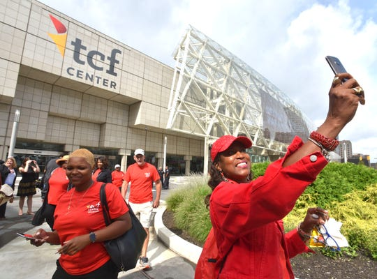 Gina Peoples, right, of Detroit, a volunteer with The Parade Company, takes a selfie Monday in front of the newly named TCF Center in downtown Detroit.