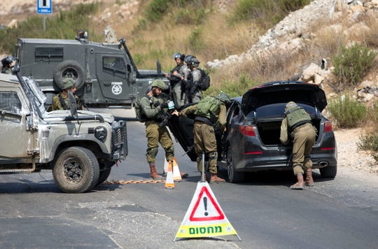 Israeli forces search of Palestinian vehicle near the area of an attack, west of the West Bank city of Ramallah, Sunday.