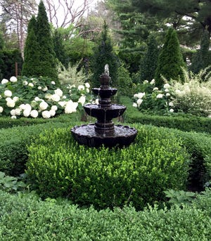 """Sue Libertiny says the fountain was added to her English-inspired garden a few years ago. Libertiny's photo, """"Boxwood and Hornbeam,"""" is this week's winner of the Homestyle Garden Photo Contest."""