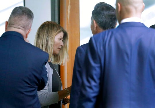 Lori Laughlin, second from left, and her husband Mossimo Giannulli, second from right, enter the back door at federal court Tuesday, Aug. 27, 2019, in Boston, for a hearing in a nationwide college admissions bribery scandal.