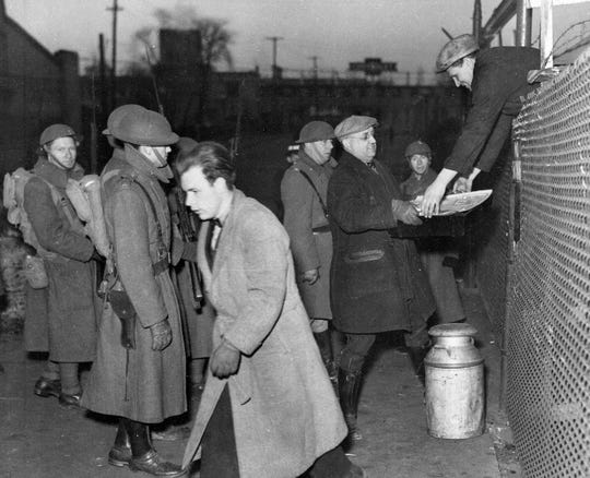 An unidentified sit-down striker reaches over a fence to receive food during the 43-day strike by autoworkers in Flint in February 1937.  Guarding the proceedings at Gate 4 of the Chevrolet plant are members of the National Guard.