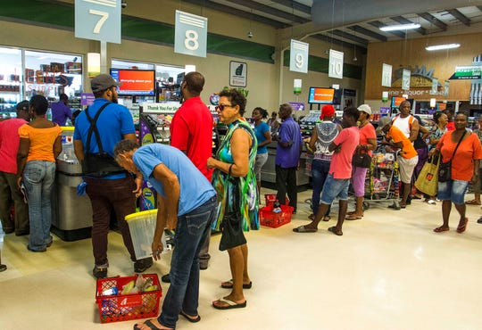 Residents stand in line at a grocery store as they prepare for the arrival of Tropical Storm Dorian, in Bridgetown, Barbados, Monday.