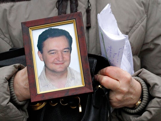 In this Nov. 30, 2009, file photo a portrait of lawyer Sergei Magnitsky, who died in jail, is held by his mother Nataliya Magnitskaya, as she speaks during an interview with the AP in Moscow. A top European court says Russia's failure to provide adequate medical care to jailed lawyer Sergei Magnitsky could have led to his 2009 death, which led to U.S. and European sanctions.