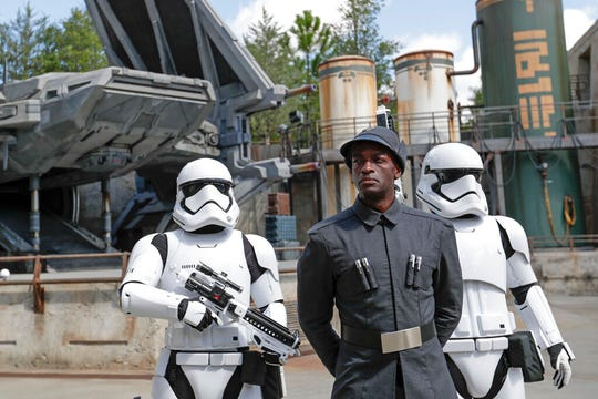 A First Order officer, center, and two storm troopers on patrol during a preview of the Star Wars themed land, Galaxy's Edge.
