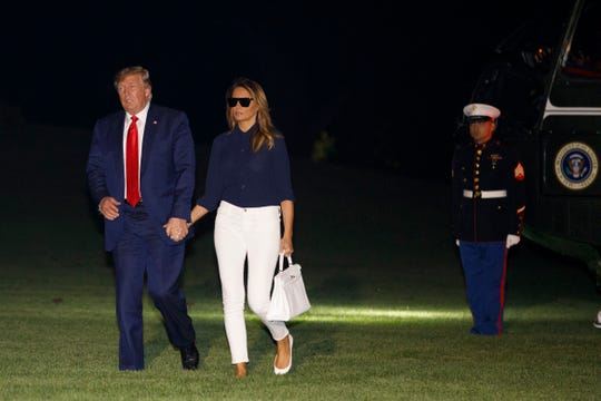 President Donald Trump and first lady Melania Trump walk to the White House, Monday, Aug. 26, 2019, as they return from attending the G-7 summit in Biarritz, France.