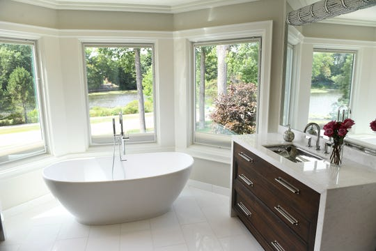 The freestanding bath tub is surrounded by windows with raisable shades in the master bath.