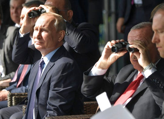 Russian President Vladimir Putin, left, and Turkish President Recep Tayyip Erdogan, 2nd right, watch planes during the MAKS-2019 International Aviation and Space Show in Zhukovsky, outside Moscow, Russia, Tuesday, Aug. 27, 2019. Putin showed off Russia's latest stealth warplane to his Turkish counterpart Recep Tayyip Erdogan, who's been barred from buying a new U.S. fighter jet by Trump.