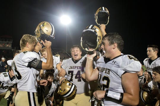 Jasper's Jackson Kabrick, left, Carter Gentry and Gabe Lehane celebrated defeating Southridge 35-7 last season in the annual battle for the Goal Posts Trophy.