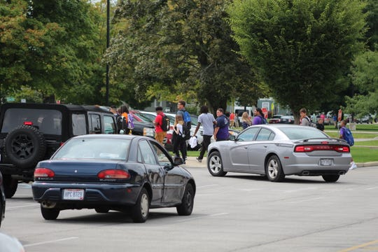 Cars leave Ross High School after they lined up in the parking lot.