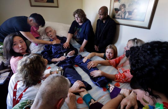 In this May 10, 2019, photo, Robert Fuller lies unconscious after plunging prescribed drugs to end his life into his feeding tube as his husband, Reese Baxter, upper left, and friends lay hands on him, in Seattle. Earlier in the day, Fuller had the party of a lifetime. He's one of about 1,200 people who have used Washington's Death with Dignity Act to end their lives in the decade since it became law. (AP Photo/Elaine Thompson)