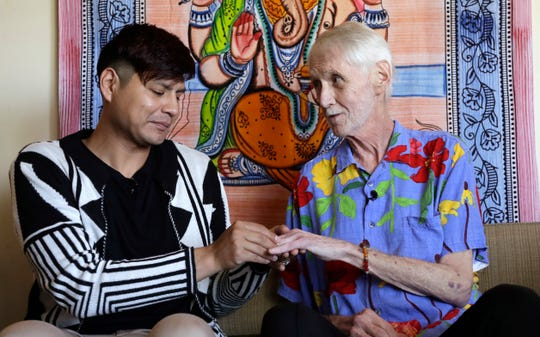 In this May 10, 2019, photo, Reese Baxter, left, puts a ring on the finger of Robert Fuller during their wedding at their home in Seattle. Later that day, Fuller plunged two syringes filled with a fatal drug cocktail into a feeding tube in his abdomen. He's one of about 1,200 people who have used Washington's Death with Dignity Act to end their lives in the decade since it became law. (AP Photo/Elaine Thompson)