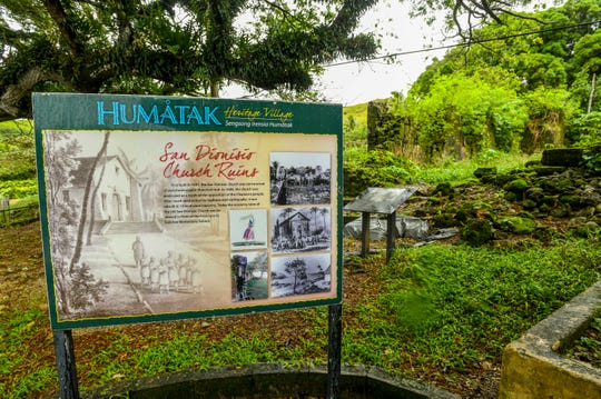 An informational sign and a plaque, seen in the background, mark the location of the San Dionisio Areopagita Church ruins on Saturday, Aug. 24, 2019. The ruins of the church first built in 1681, is located along Route 2 in Umatac, near the former F. Q. Sanchez Elementary School.