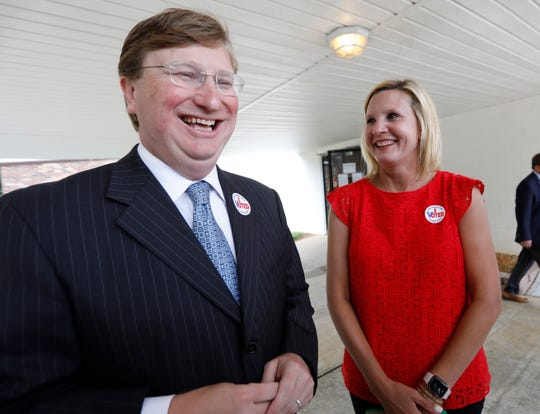 Lt. Gov. Tate Reeves, left, and his wife Elee Reeves, share a laugh as he speaks with reporters about the final days of the runoff campaign, for the GOP nomination for governor, Tuesday, Aug. 27, 2019 at his Flowood, Miss., voting precinct. Reeves faces former Mississippi Supreme Court Chief Justice Bill Waller Jr., for the party's nomination.