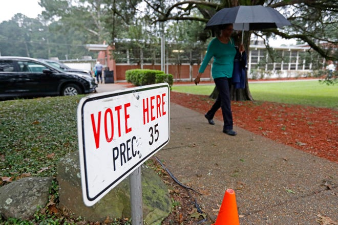 A voter rushes to her car after voting as rain begins to pick up outside a north Jackson, Miss., precinct, Tuesday, Aug. 27, 2019. Featured among the GOP runoff races are contests for the gubernatorial nomination and attorney general.