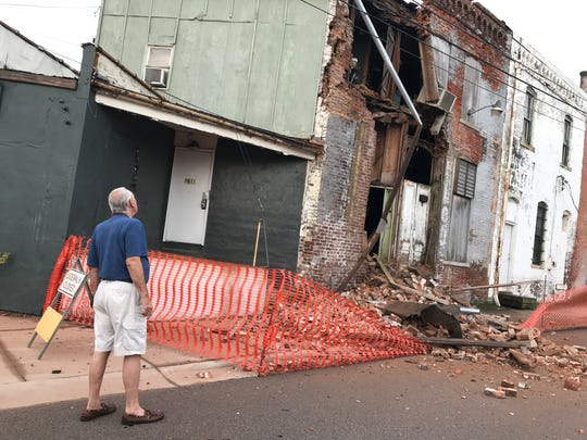 Building owner Dan Vierk checks the damage Tuesday morning after part of the E.M. Weaver Building at Main and South streets collapsed.