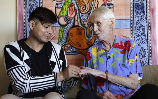 In this May 10, 2019, photo, Reese Baxter, left, puts a ring on the finger of Robert Fuller during their wedding at their home in Seattle. Later that day, Fuller plunged two syringes filled with a fatal drug cocktail into a feeding tube in his abdomen. He's one of about 1,200 people who have used Washington's Death with Dignity Act to end their lives in the decade since it became law.