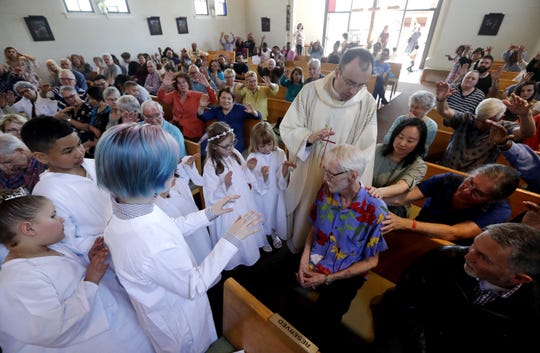 In this May 5, 2019, photo, Robert Fuller, seated center right, receives a blessing and prayer from Rev. Quentin Dupont, white-robed children who had just received their first communion and the congregation at St. Therese Parish Catholic church in Seattle. Just days later, the day he picked to die, Fuller had the party of a lifetime. Then later that afternoon, he plunged two syringes filled with a fatal drug cocktail into a feeding tube in his abdomen.