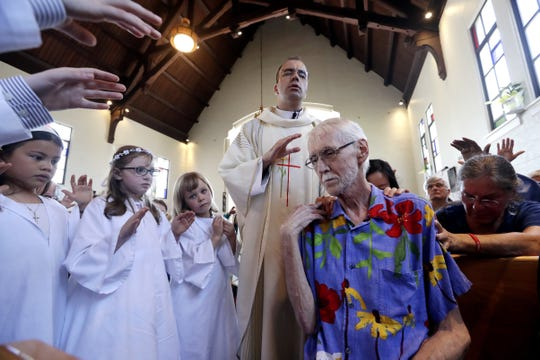 In this May 5, 2019, photo, Robert Fuller, foreground right, receives a blessing and prayer from Rev. Quentin Dupont, white-robed children who had just received their first communion and the congregation at St. Therese Parish Catholic church in Seattle. Just days later, the day he picked to die, Fuller had the party of a lifetime. Then later that afternoon, he plunged two syringes filled with a fatal drug cocktail into a feeding tube in his abdomen. He's one of about 1,200 people who have used Washington's Death with Dignity Act to end their lives in the decade since it became law.