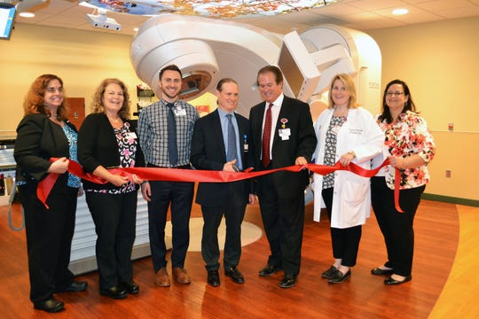 St. Joseph Mercy Brighton Cancer Center  officials and doctors unveil a Varian True Beam Linear Accelerator, in this June 2018 photograph. The health center is one of 13 locations gaining access to clinical cancer trials due to a $19.3 million federal grant from the National Center Institute.