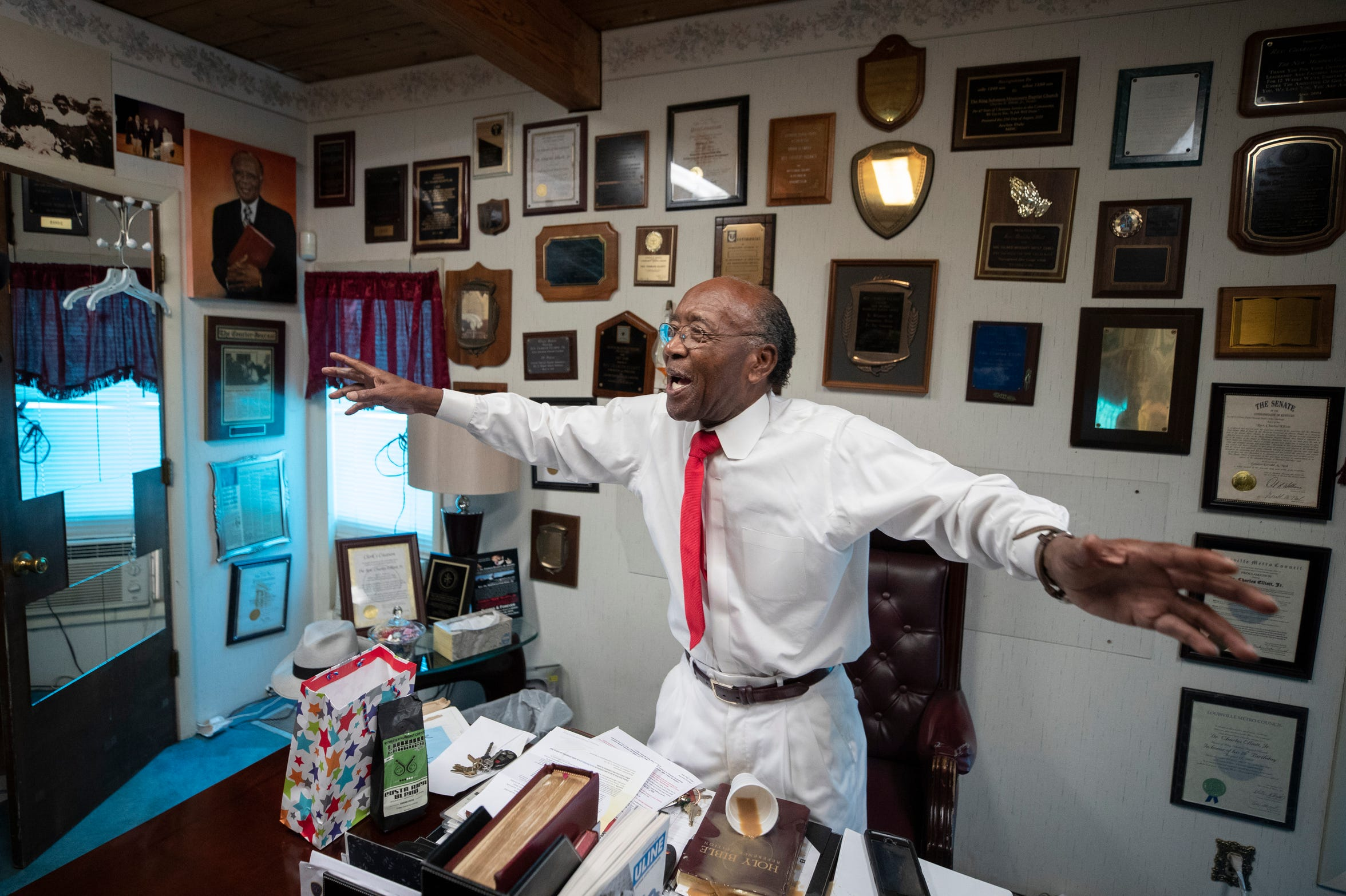 The Rev. Charles Elliott Jr. gestures as he tells a story in his office at King Solomon Missionary Baptist Church, knocking over his cup of coffee. Aug. 25, 2019.