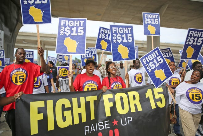 Members of the Wisconsin Jobs Now group, representing Fight For 15, which favors a $15 an hour minimum wage, march down E. Chicago St. shortly before entering the Summerfest grounds for Labor Fest in 2015.
