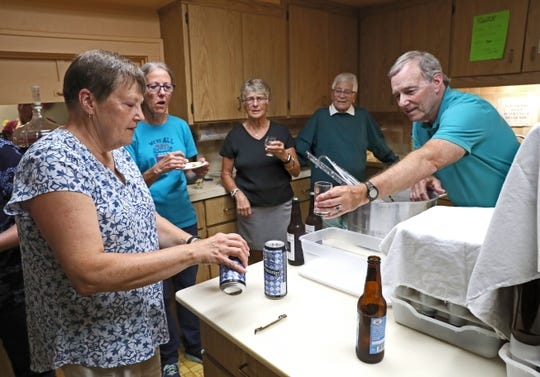Barley Ministries Brewing members  sample Oktoberfest beers while they bottle the beer they made at their church, the First Congregational United Church of Christ in Elkhorn. The group  includes Barb Townsend, pouring, Bob Burton, leaning forward with his glass, along with, left to right, Carol Prchal, Nancy Morgan and Ann Serpe.