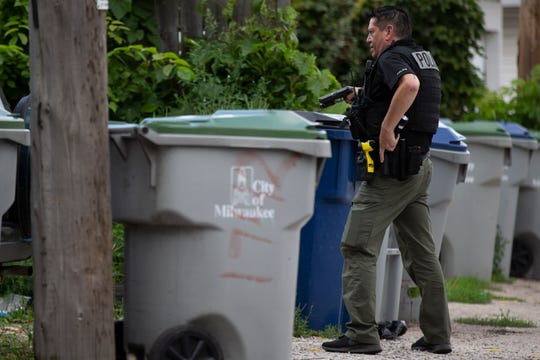 Milwaukee police search for evidence during a manhunt near 22nd Street and Maple Avenue in Milwaukee on Tuesday, Aug. 27, 2019.
