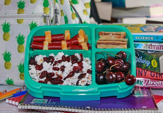 This Wisconsin product lunch box features popcorn and dried cranberries; whole cherries; kebabs made with chunks of Colby jack cheese and sausage; and slices of apple kringle, upper right.