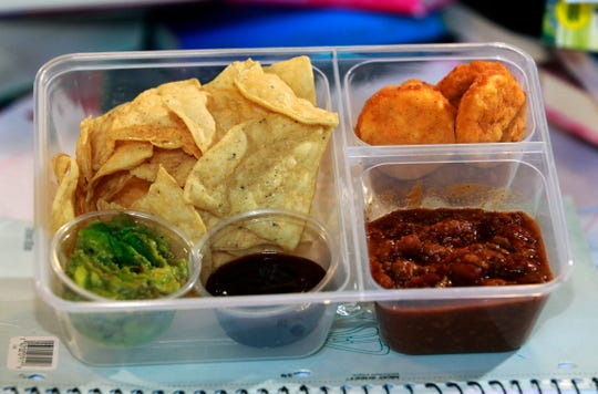 This tailgating lunch box  features tortilla chips with guacamole for dipping, left; chili; and chicken nuggets, upper right,  with barbecue sauce for dipping.