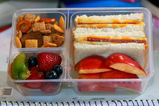 This KwikTrip lunchbox  features  a sandwich (salami with cheese slices surrounding it) and white bread; Chex Mix, upper left, apples slices and a fruit cup that had strawberries, kiwi and blueberries.