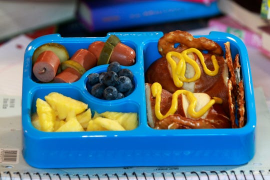 This Brewer/Miller Park lunch box  features a halved pretzel bun with mustard on it, along with pretzel chips, right; skewers with sliced hot dogs and pickle slices, upper left; sliced pineapple; and blueberries.