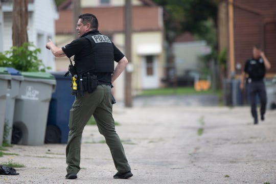 Milwaukee police officers search for evidence during a manhunt near 22nd Street and Maple Avenue in Milwaukee on Tuesday, Aug. 27, 2019.