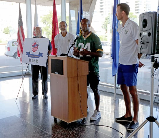 Former Green Bay Packer Jarrett Bush speaks Tuesday during an announcement about Wisconsin sports teams that will be involved in Stars and Stripes Honor Flights. With Bush are from left, former Brewers pitcher and current broadcaster Jerry Augustine, former Bucks player Dick Garrett and former Bucks player and current broadcaster Steve Novak.