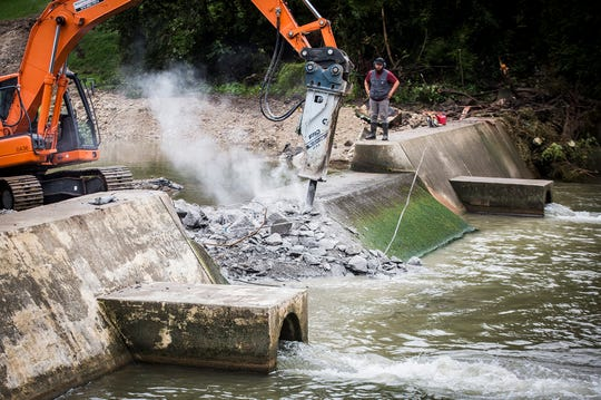 A construction crew breaks apart a dam near McCulloch Park in the White River. The City, with help from the DNR, is removing the dam to help local wildlife.