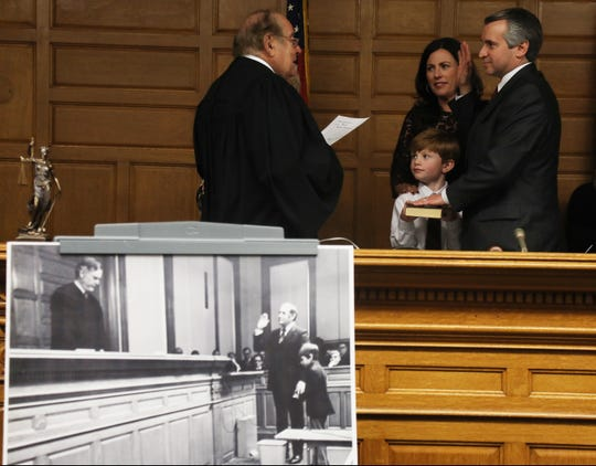 An old black and white photo in front of the bench depicts Thomas Rumana, Scott's father being sworn in as a judge in 1972 as Scott holds the Bible.  Behind the photo, Thomas Rumana swears in his son Scott as a Superior Court judge in December of 2016 as Tommy Rumana, Scott's son, holds the Bible. Scott's wife Laura is there as well.