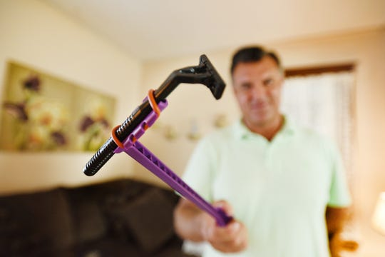 """Charles Bolcar, retired Clifton Fireman, shows his patented item called """" Ape Scrape"""", a hairy back shaver, photographed at his home in Nutley on 08/26/19. It is used to shave hair from  the back."""