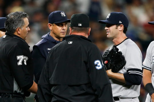 Yankees relief pitcher Cory Gearrin (right) speaks with umpire Manny Gonzalez.