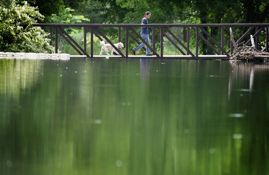 A woman walks her dog over a footbridge at Goffle Brook Park in Hawthorne on Aug. 27.