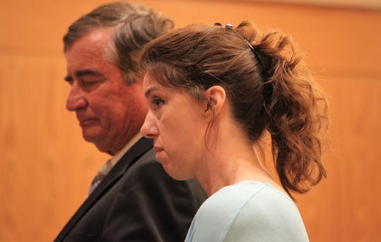 Kimberly Yacone, standing with her attorney, George Harrison, answered questions about her husband's criminal history during a hearing over Forghedaboudit restaurant's liquor license during the Doña Ana County Board of Commissioners meeting on Tuesday, Aug. 27, 2019.