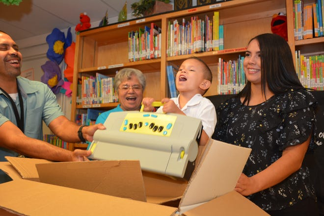 Alex Gonzalez, 7, first grader at Gadsden ISD's Riverside Elementary, shouts with joy as he pulls out his own top of the line braille machine, the Mountbatten Whisperer Learning System, which was donated to him for home use by the New Mexico Lions Eye Foundation.