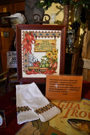 This framed needlepoint by Holly Fawcett featured at the Catwalk Gallery is a fundraiser for Glenwood Community Library.