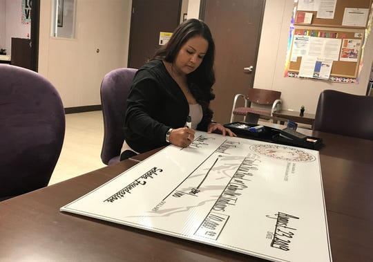 Geneva Mojado, president of the Soboba Foundation and Soboba Band of Luiseño Indians tribal member, writes a check for $10,000 for the Santa Rosa Band of Cahuilla Indians. The tribe will put the donation toward construction of a new park on the reservation in Mountain Center.