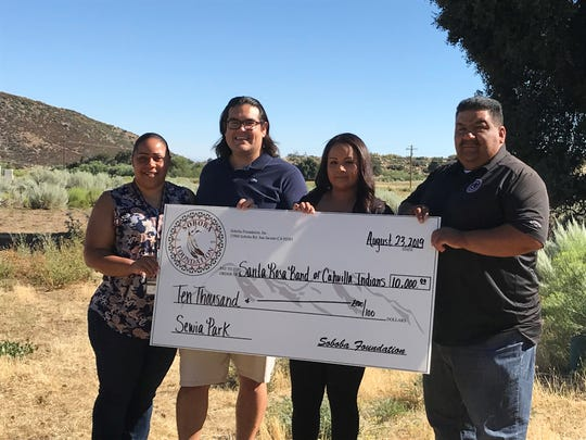 From left to right, Vanessa Minott, Santa Rosa Band of Cahuilla Indians tribal administrator; Steven Estrada, Santa Rosa tribal chairman; Geneva Mojado, Soboba Foundation president; and Isaiah Vivanco, Soboba Band of Luiseño Indians tribal vice chairman, display a check awarded to the Santa Rosa tribe on its reservation on Aug. 23, 2019. The group stands at the future location for the park.