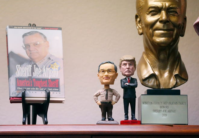 Side-by-side bobbleheads of Joe Arpaio and Donald Trump in Arpaio's home office.
